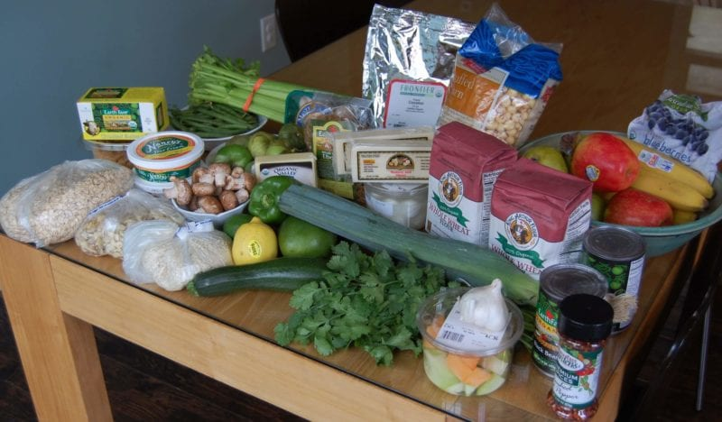Groceries from Earth Fare that include fruits and vegetables, flour, frozen berries, cheese, oats, and more.