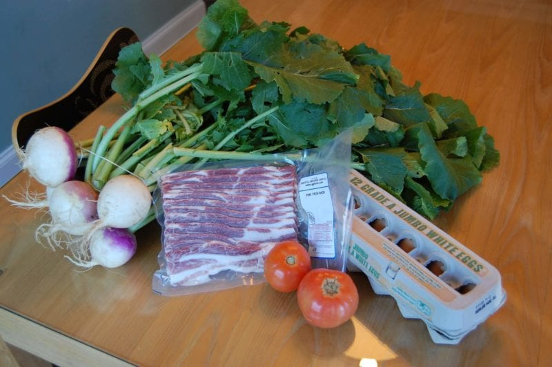 Groceries from a local Farmers Market that includes bacon, eggs, tomatoes, and radishes.