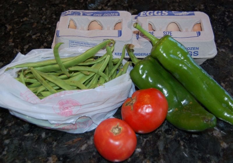 Groceries that include green beans, tomatoes, peppers, and eggs.