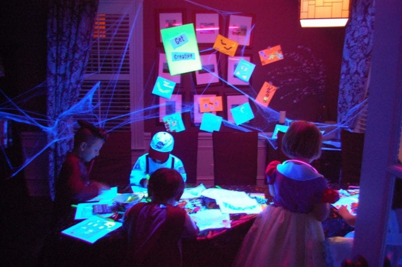 Inside of a house decorated for Halloween with kids dressed in costumes.