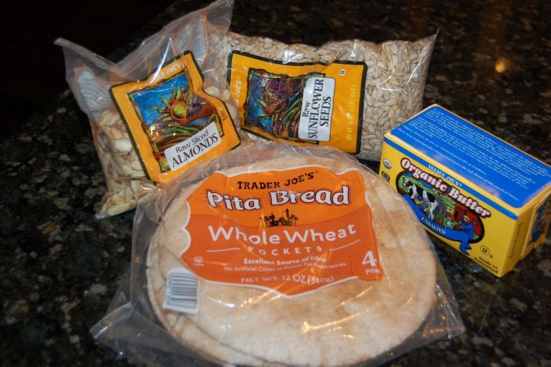Groceries from Trader Joe's that include almonds, sunflower seeds, butter, and pita bread.