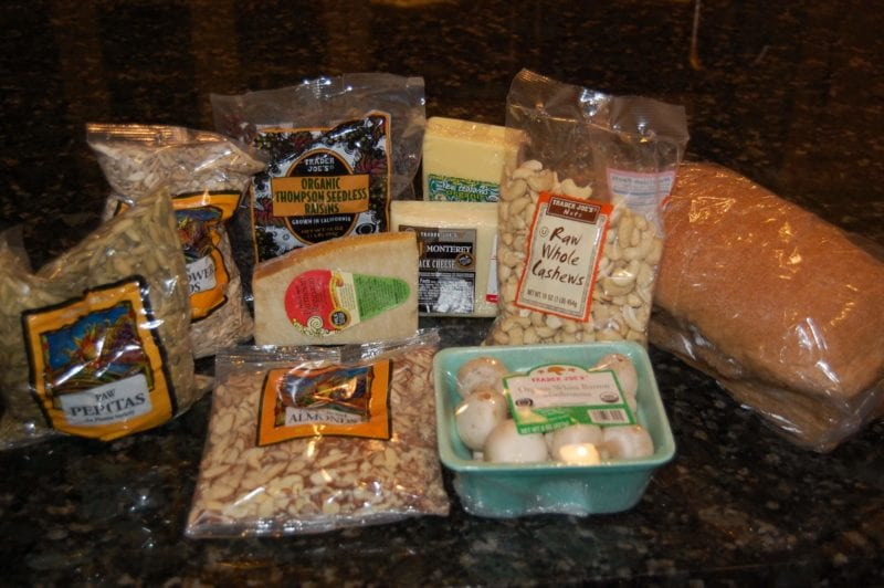 Groceries from Trader Joe's that include seeds, mushrooms, cheese, nuts, and raisins.