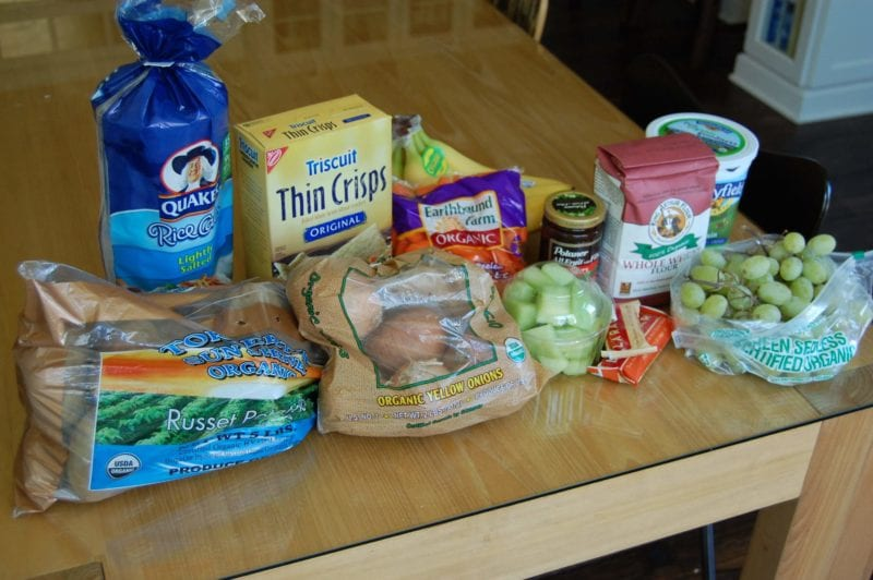 Groceries from Bi-Lo that included potatoes, onions, fruit, crackers, flour, yogurt, Lara bars, and brown rice cakes.