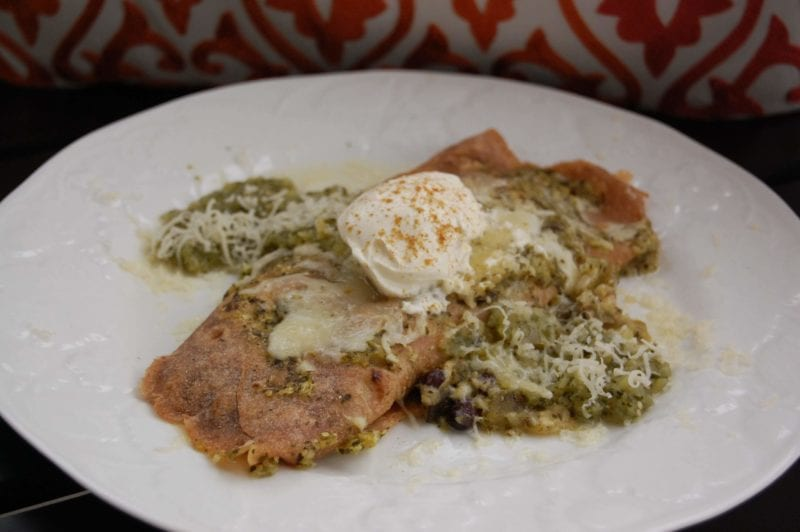 Vegetarian enchilada dish topped with homemade tomatillo salsa and cheese on a plate.