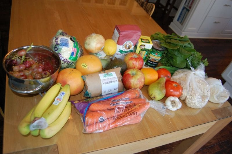 Groceries from Earth Far that include fresh produce, rolled oats, butter, flour, and chicken.