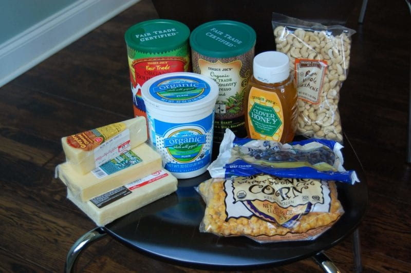Groceries from Trader Joe's that include coffee, nuts, cheese, yogurt, frozen corn and blueberries, and honey.