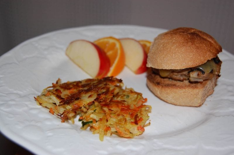 Turkey burgers, veggie pancakes, and fruit on a plate.