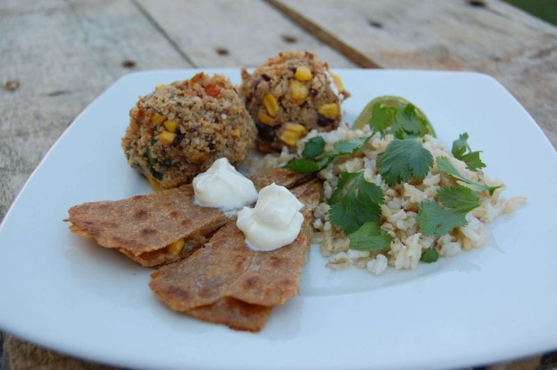 Black bean croquettes, brown rice, and quesadillas on a plate.
