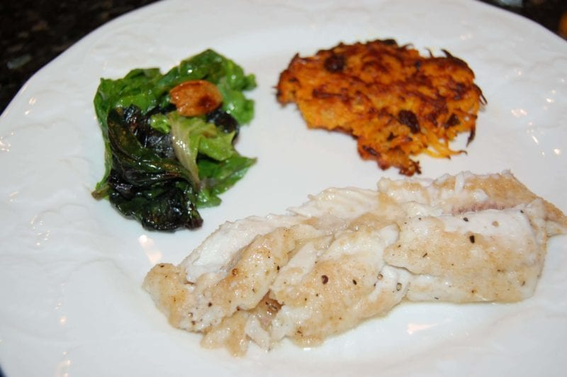 White fish with a side of sweet potato pancakes and greens on a plate.