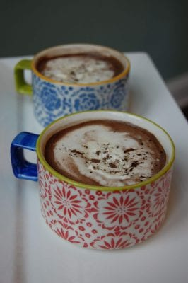 Two decorative cups of homemade mocha hot chocolate.