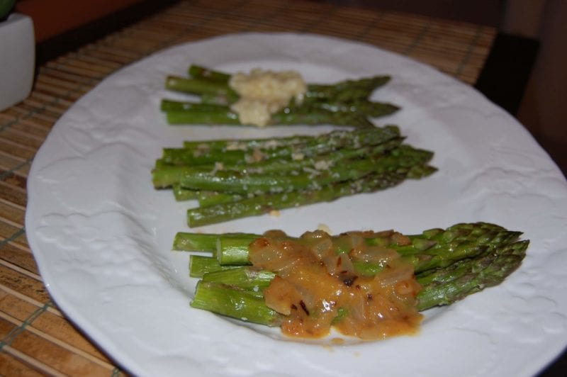 A plate of asparagus prepared with three different toppings.