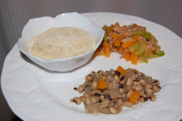 Plate of black-eyed peas for New Year's Day with a side of polenta and homemade stuffing.