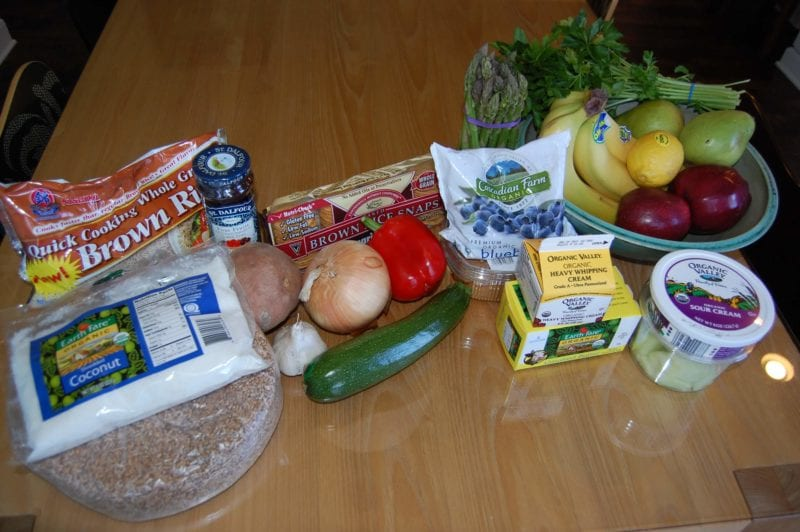 Groceries from Earth Fare that include fresh produce, frozen blueberries, brown rice, shredded coconut, sour cream, and heavy cream.