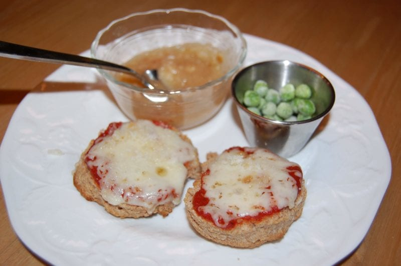 Homemade pizza biscuits, frozen peas, and a side of applesauce.