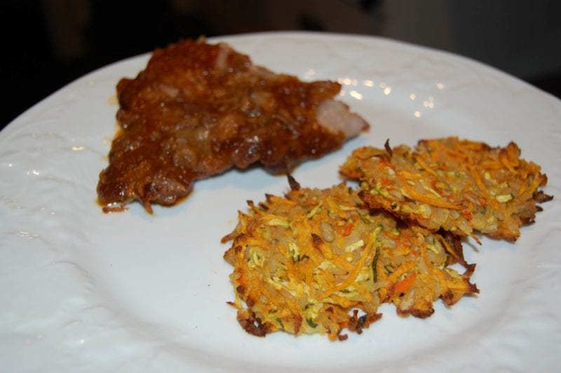 Pork ribs made in the slow cooker and brown rice patties on a plate.