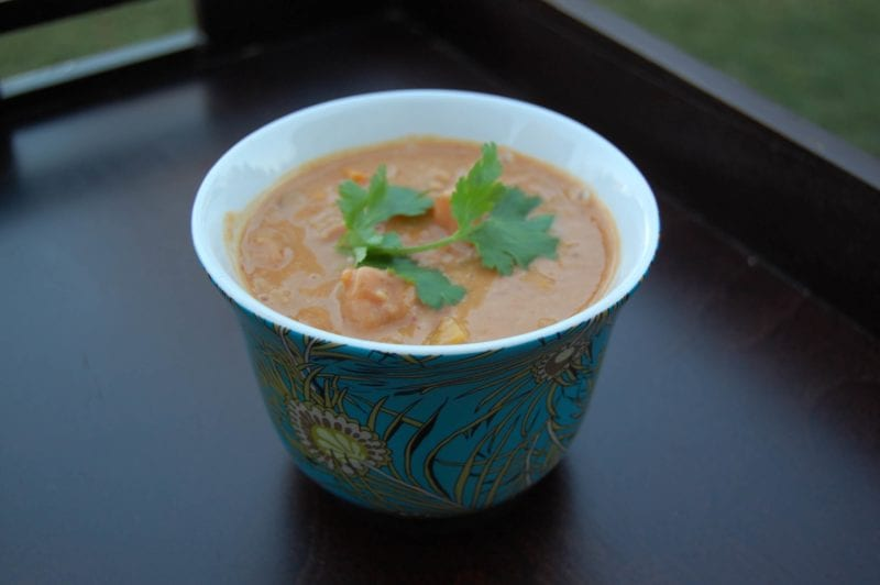 Homemade squash peanut soup topped with cilantry in a decorative bowl.