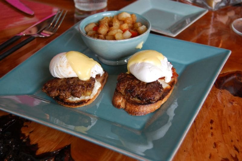 Eggs benedict with pasture-raised, house-crafted lamb sausage, warm chevre, romat tomatoes, and a poached egg over a toasted fresh-made baguette from Halcyon in North Carolina.