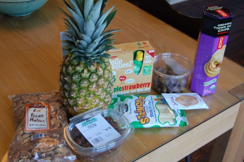 Groceries from Earth Fare that include pineapple, string cheese, pecans, dates, Squeeze applesauce, peanut butter, olives, and brown rice crackers.