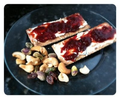 Crackers with cream cheese and nuts are a healthy snack idea
