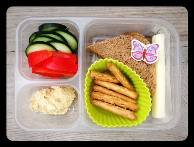 Sunflower seed butter and honey sandwich, whole-grain pretzels, organic cheese stick, cucumbers, red bell peppers, and hummus (for dipping)