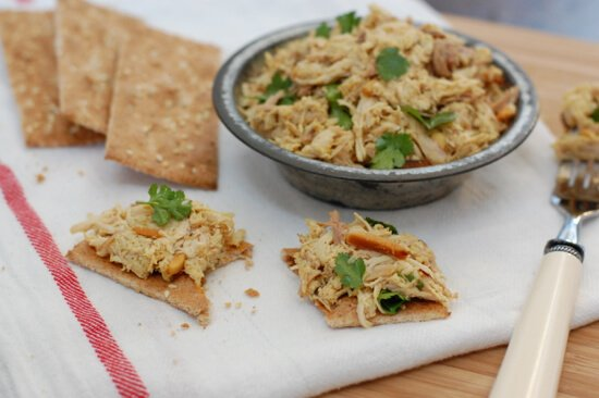 Curry Chicken Salad in a bowl and a few crackers topped with the chicken.
