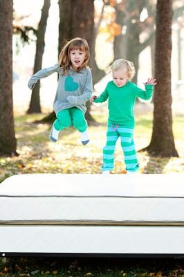 Emily and one of her sisters jumping around on a mattress by My Green Mattress