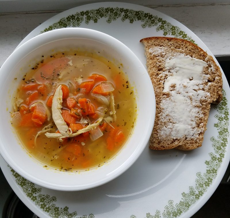 Chicken & carrot soup with homemade whole wheat bread with butter on top