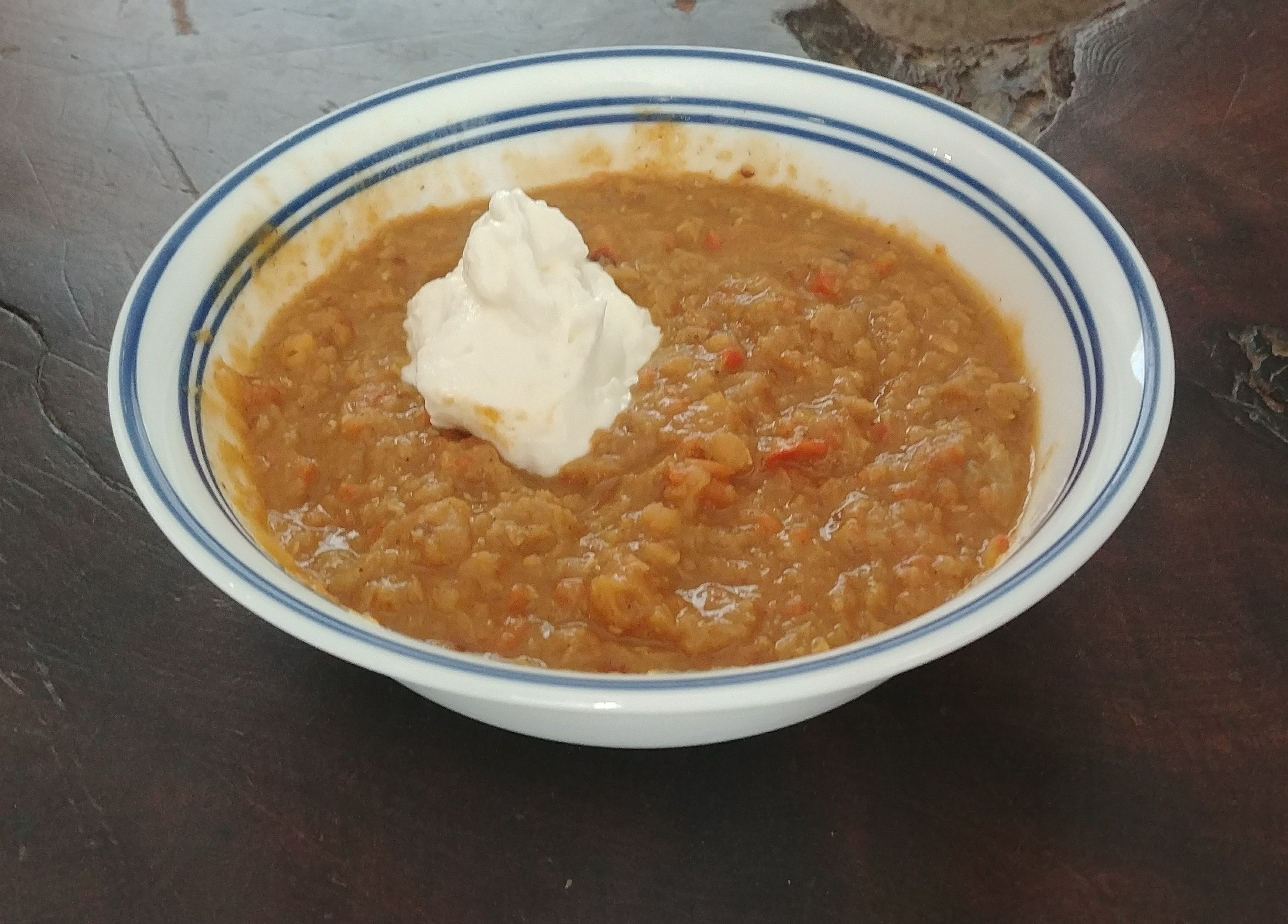 Red lentil soup topped with plain greek yogurt and a Babybel cheese