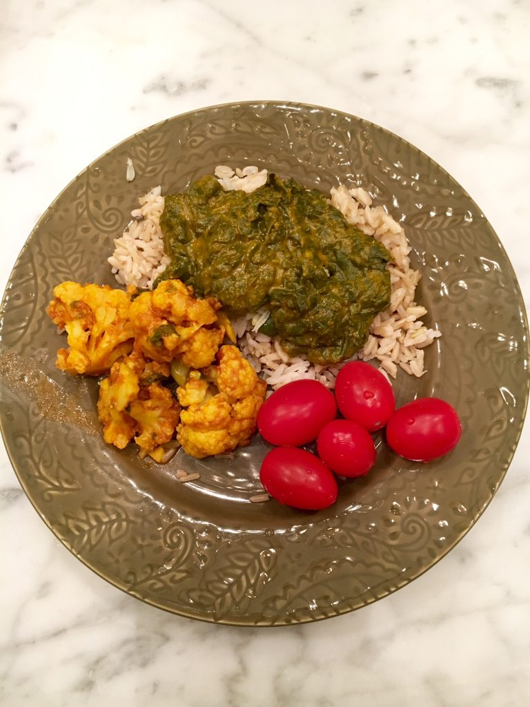 Food Diary:Indian-cooked cauliflower & potatoes (Gobi) and Saag (Indian-cooked spinach & mustard greens) with brown rice and tomatoes on the side.