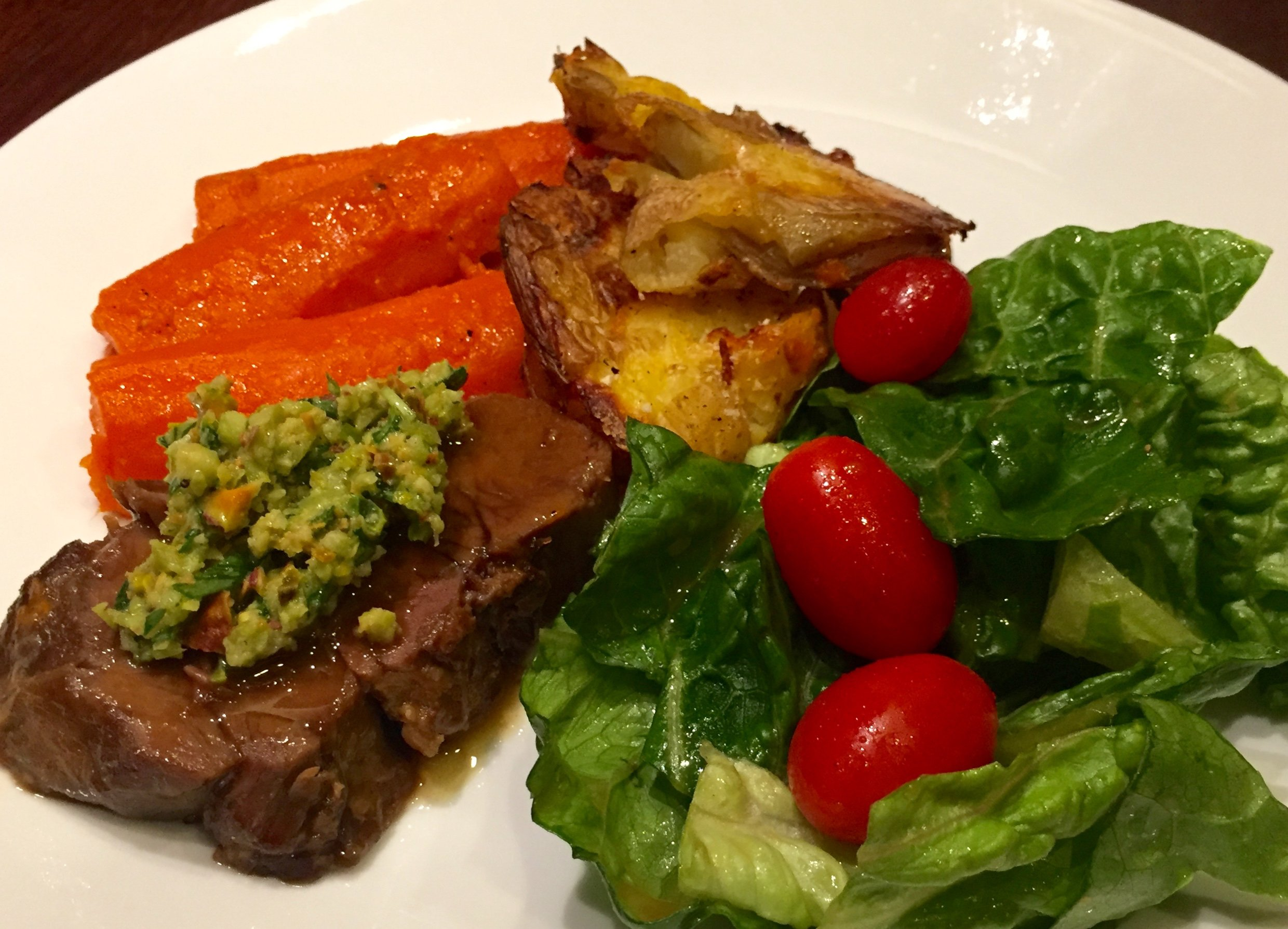 salad with cherry tomatoes, olive oil, mustard, maple syrup, balsamic vinegar - leg of lamb with olives, pistachios, tarragon, lemon, garlic - caramelized carrots - roasted potatoes
