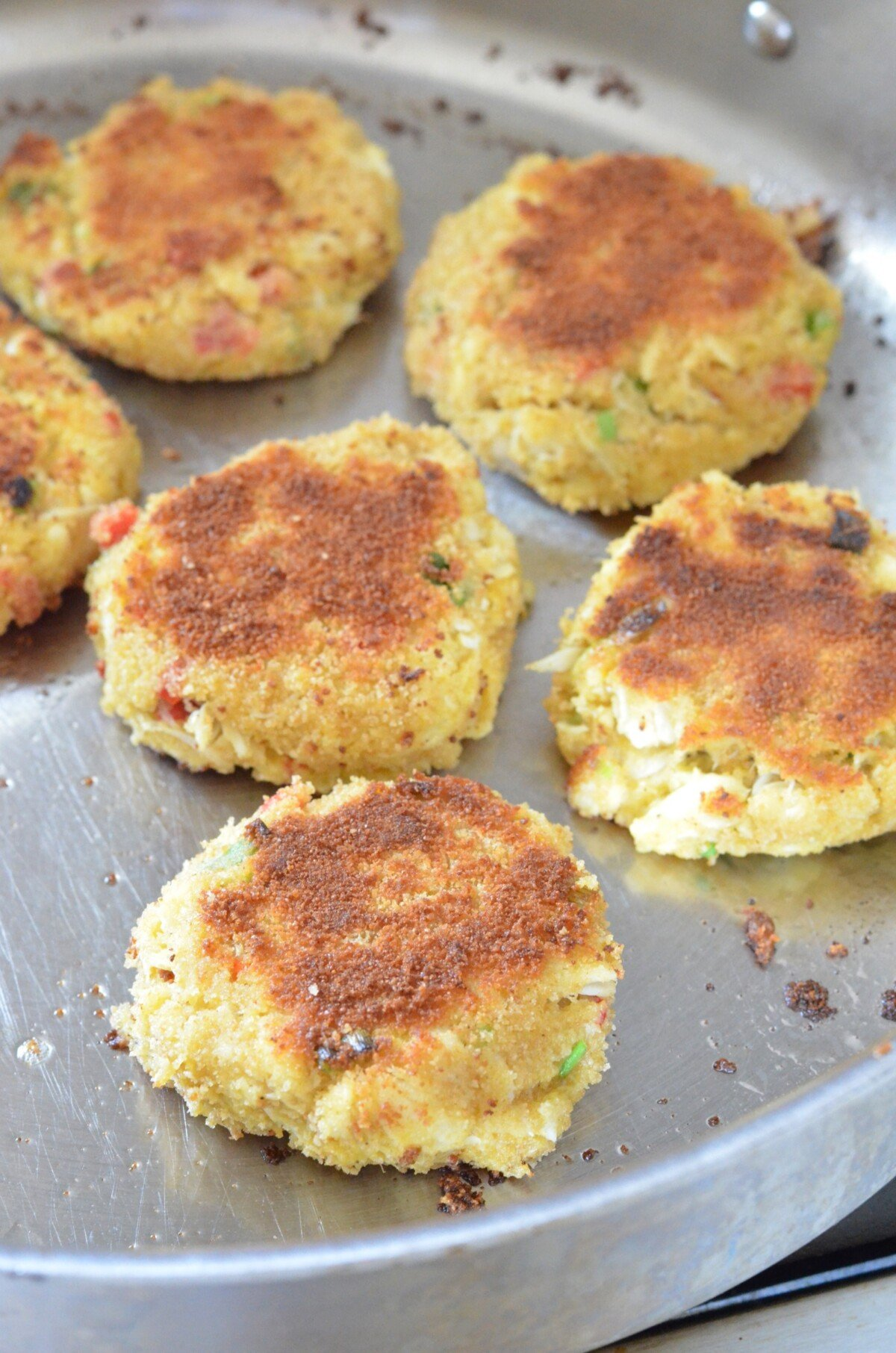 Crab Cakes being made in a frying pan.