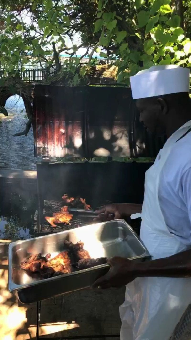 Chef removing Jerk Chicken from grill in Jamaica on 100 Days of Real Food