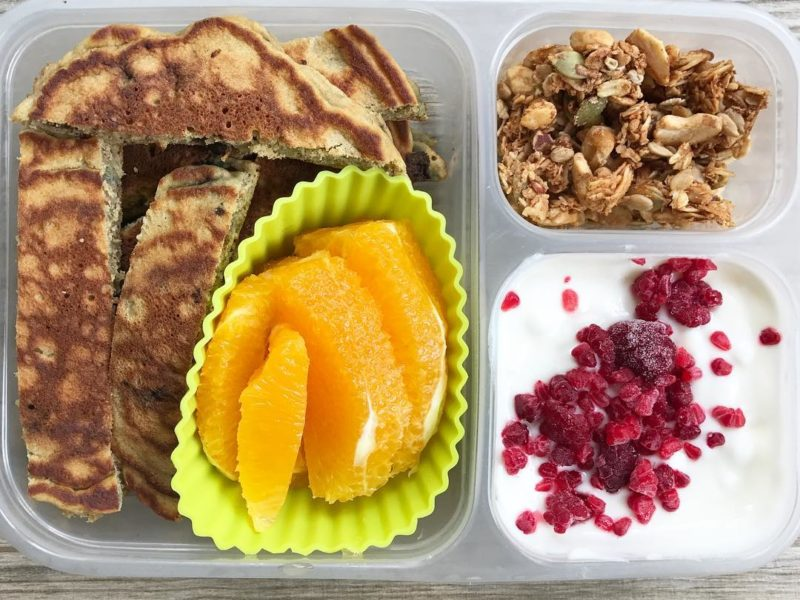 Homemade whole wheat blueberry pancakes, Oranges, Plain yogurt with maple syrup and frozen raspberries, Homemade granola - School Lunch Roundup 12 on 100 Days of Real Food