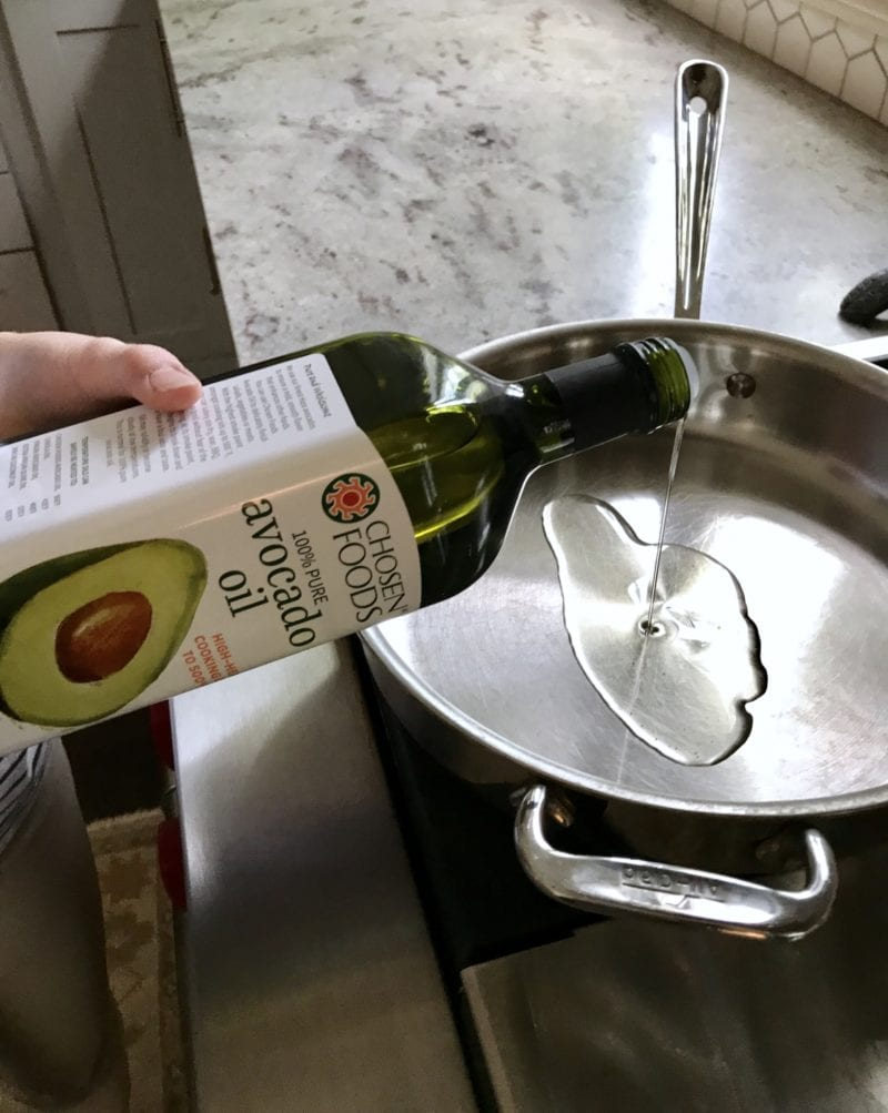 Pouring avocado oil into a saute pan
