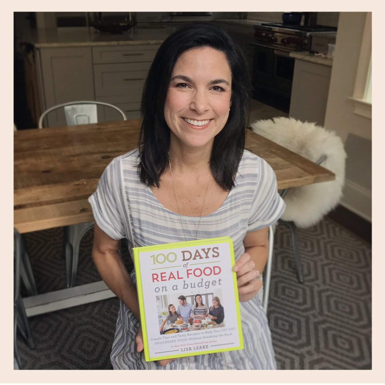 "Author Lisa Leake holding a copy of her new ""100 Days of Real Food: On a Budget"" cookbook"