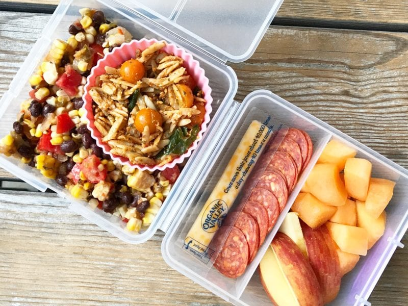 Pasta Salad with Red Pepper Pesto in lunch box as side with black beans, corn, tomato dish, cheese stick, pepperoni slices, and fresh fruit slices