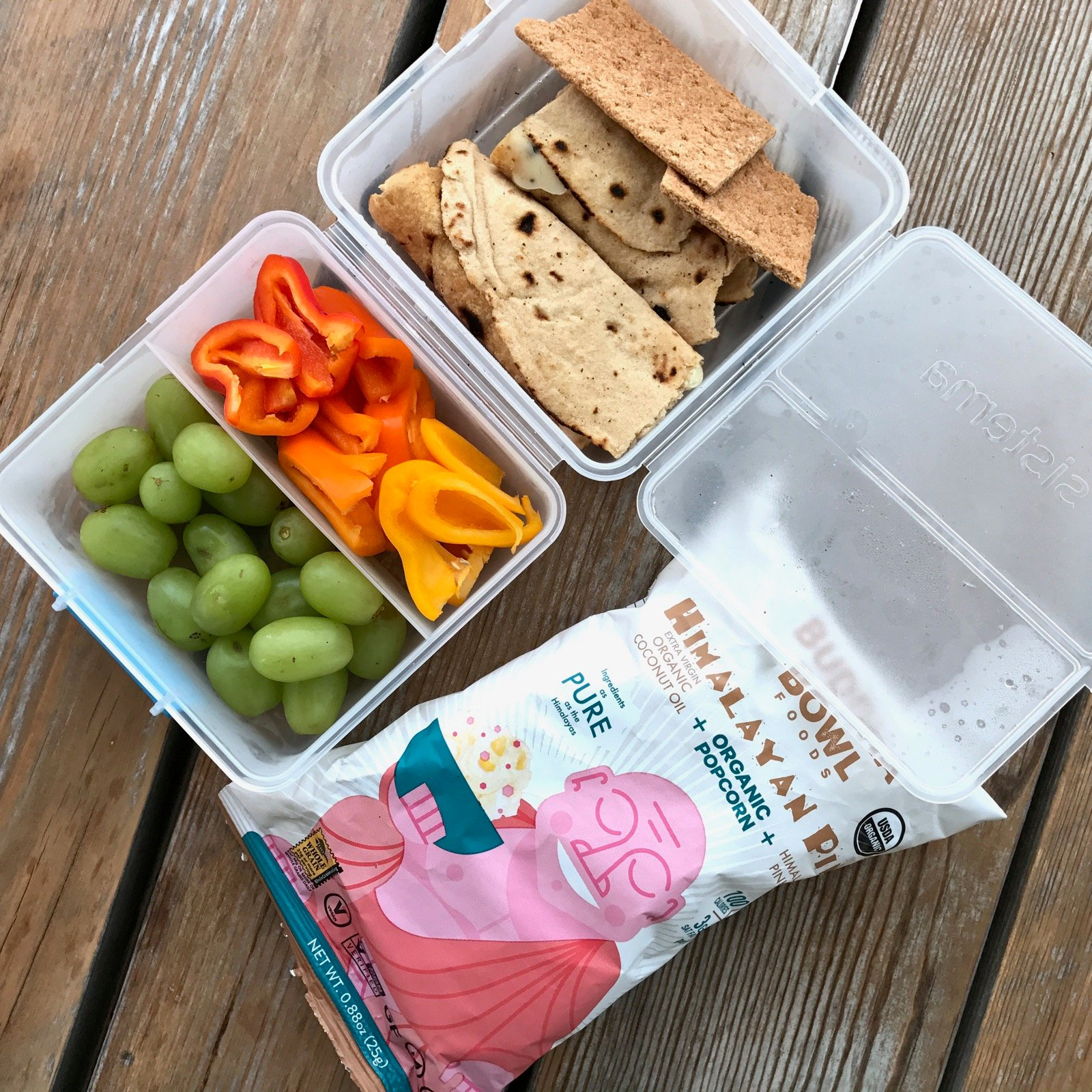 Packed school lunch of Cheese melted in a whole-wheat tortilla, 2 whole-wheat cinnamon graham crackers, Sliced bell peppers, Grapes, Bag of popcorn
