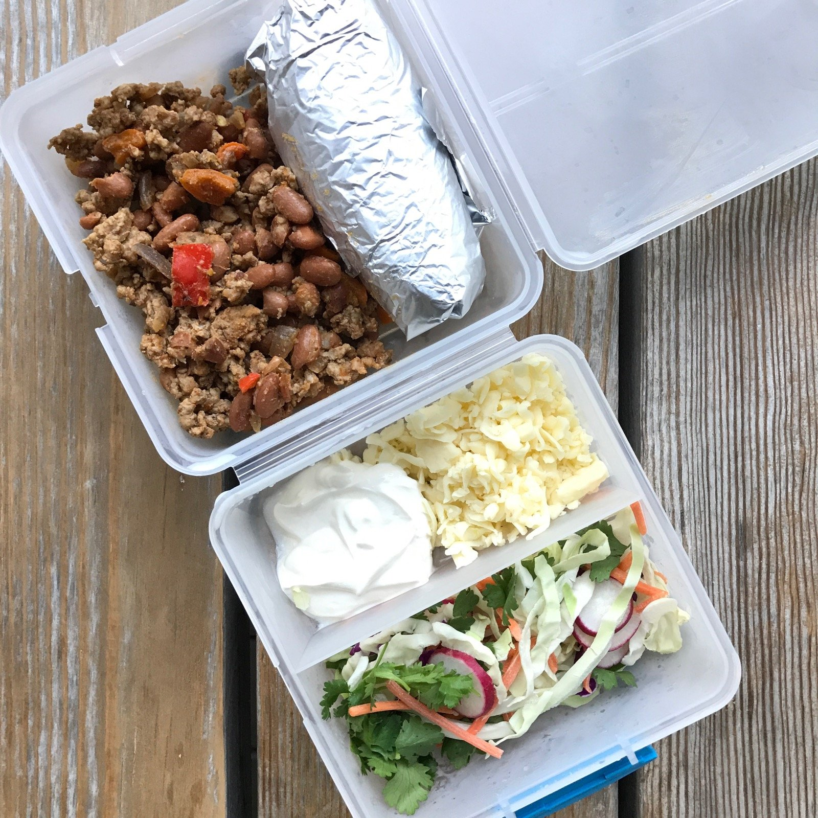 Packed school lunch of Leftover taco meat/veggies/beans, Corn tortilla (in foil), Sour cream Cheese Cabbage, cilantro and other veggies to go on top