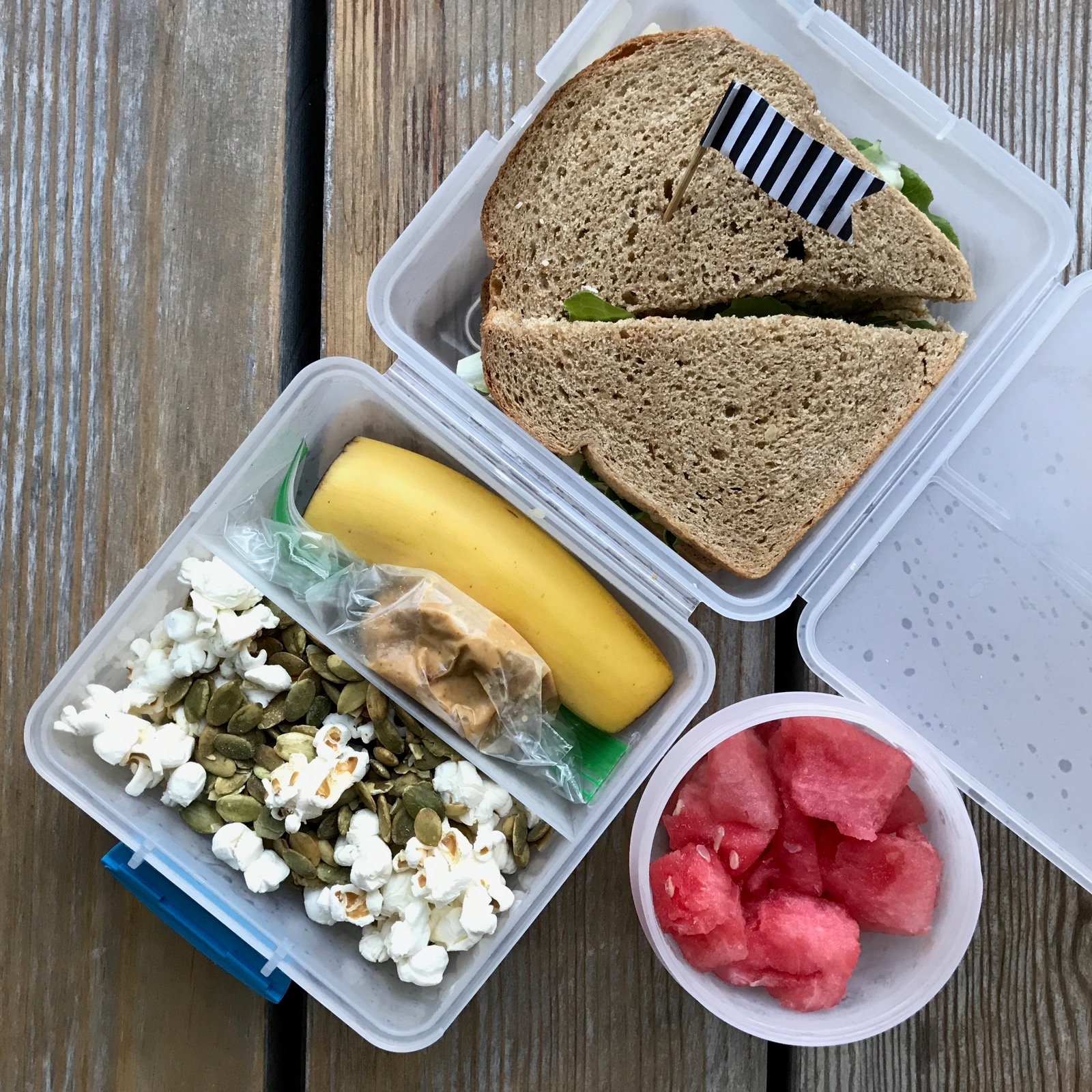 Packed school lunch of Hummus, cheese and lettuce sandwich Banana and PB Popcorn and roasted pumpkin seed mix Watermelon