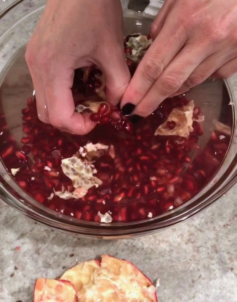 Extracting pomegranate seeds in a bowl of water