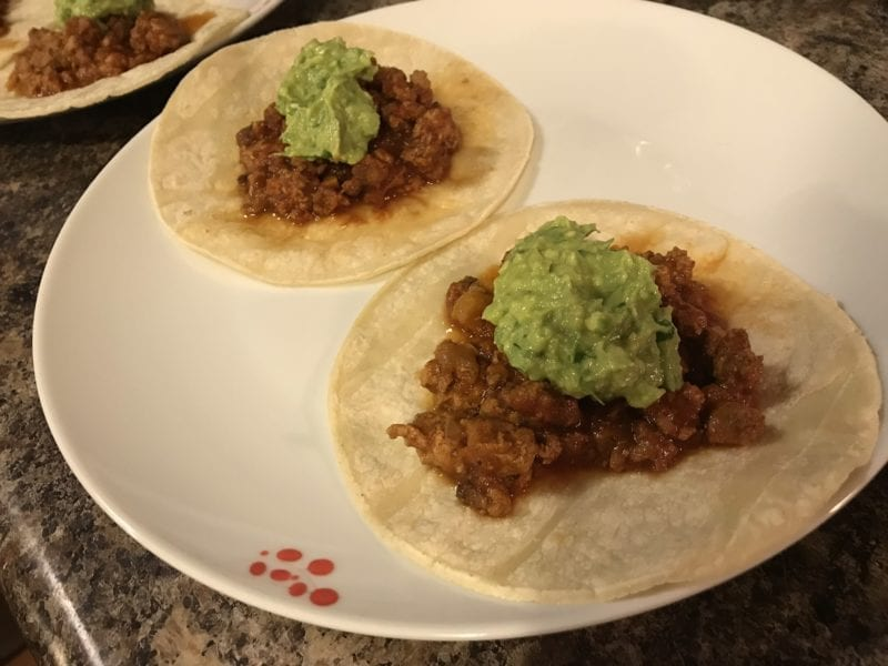 Slow cooked turkey on corn tortillas topped with homemade guacamole