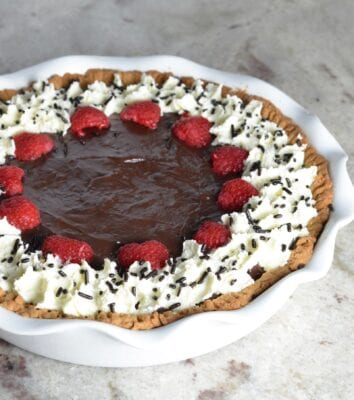 Chocolate pudding pie with raspberries, whipped cream and chocolate sprinkles.