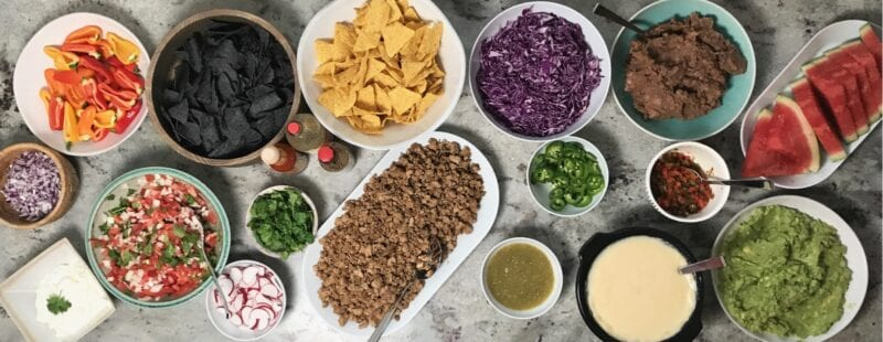 Healthier Nacho Bar on 100 Days of Real Food full of nachos, veggies, and homemade queso.
