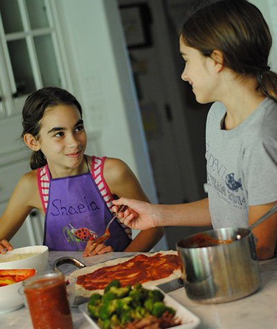 two girls cooking pizza in the kitchen for Camp Kitchen