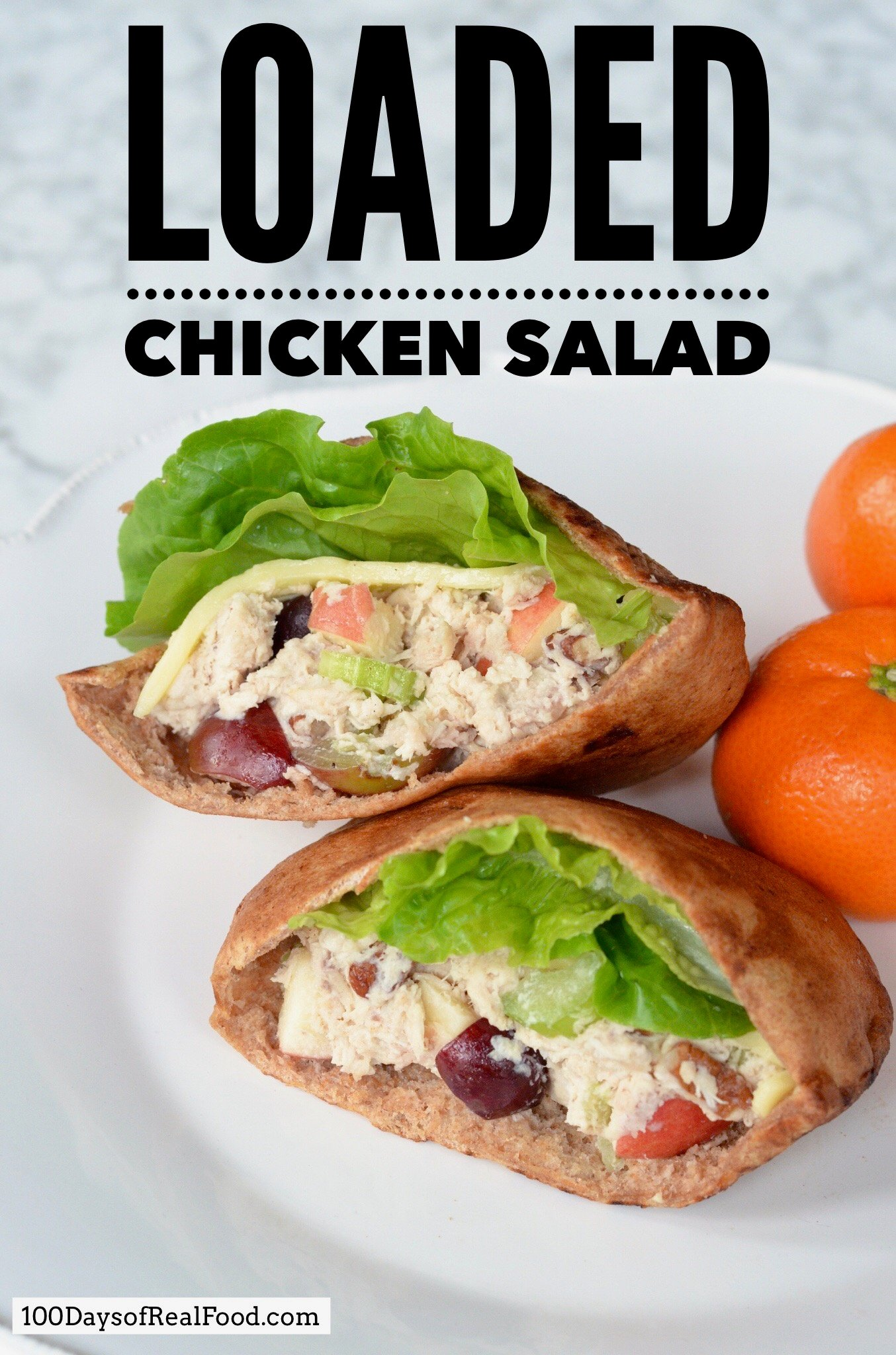 Two loaded chicken salads in pita pouches on a plate with oranges.