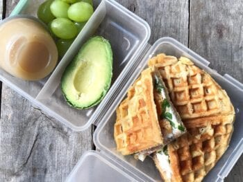 school lunch with waffle sandwich, avocado, grapes, and applesauce from 100 days of real food