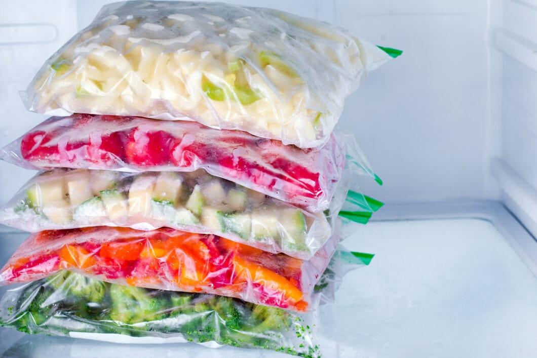 Bags with frozen vegetables in freezer