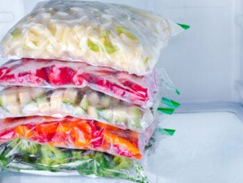 Bags with frozen vegetables in freezer