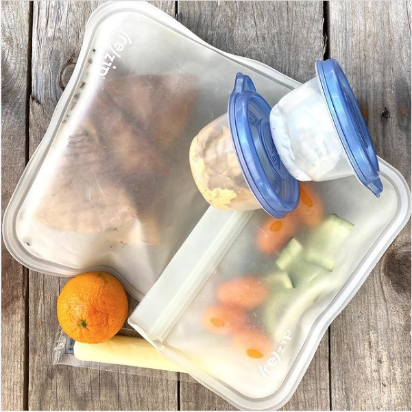 Packed school lunch that includes baked pita chips, tomatoes, cucumbers, an orange, cheese stick, and tzatziki and hummus.