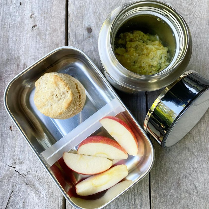 Packed school lunch that includes leftover Chicken and Broccoli Curry Casserole in a thermos, homemade biscuit and some apple slices.